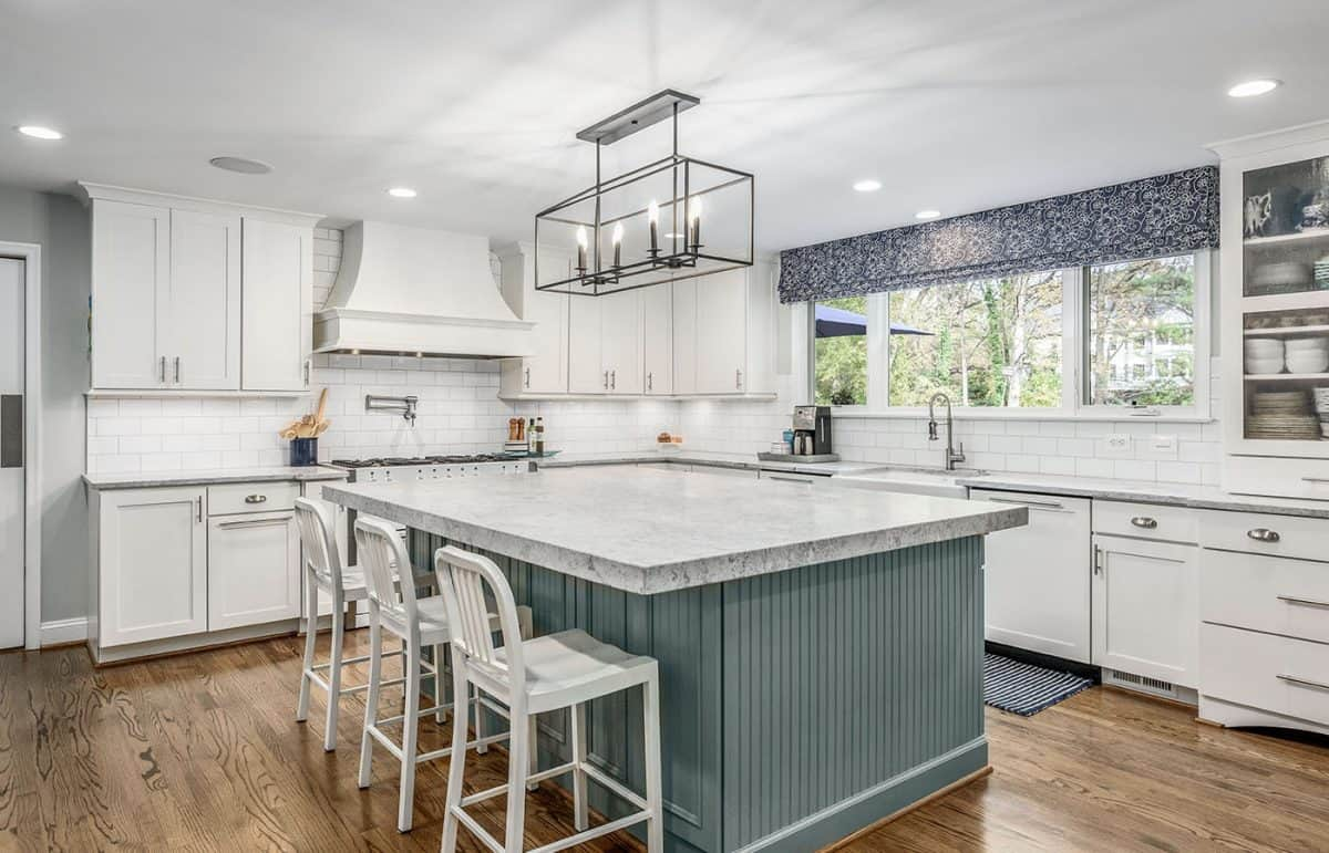 A bright kitchen with gray-blue cabinets and gray countertops