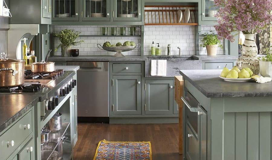 A kitchen with desaturated green cabinetry, gray countertops, white tile, and stained wood